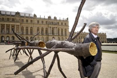 Sur l'esplanade du château, l'artiste pose à côté de son œuvre en bronze et or, «Espace de lumière» (2008). © Manuel Lagos Cid / Paris Match